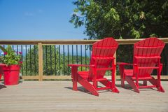 View of typical canadian red muskoka chairs on a wood deck. View of 2 empty red muskoka chairs on a wood deck, ready to enjoy the view in the canadian summer Royalty Free Stock Photography