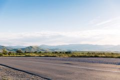 Empty asphalt road with blue summer sky and hills on background. Crimea, Koktebel. View on a typical highway on hills background. Summer time royalty free stock photos