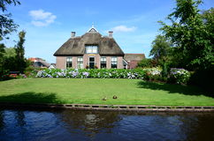 View of typical houses of Giethoorn,The Netherlands.  The beautiful houses and gardening city is know as Stock Photo
