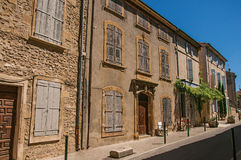 View of typical stone houses and shops on a street of Lourmarin. View of typical stone houses and shops on a street of the historical village of Lourmarin Stock Photography
