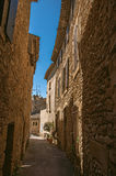 View of typical stone houses with sunny blue sky, in a narrow alley of Lourmarin. View of typical stone houses with sunny blue sky, in a narrow alley of the Royalty Free Stock Photo