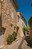 View of typical stone houses with sunny blue sky, in a raised alley of Lourmarin. View of typical stone houses with sunny blue sky, in a raised alley of the Royalty Free Stock Photo