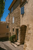 View of typical stone houses with sunny blue sky, in a raised alley of Lourmarin. View of typical stone houses with sunny blue sky, in a raised alley of the Stock Photo