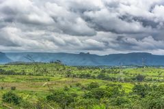 View with typical tropical landscape and electric tower and power lines. Mountains and cloudy sky as background stock image