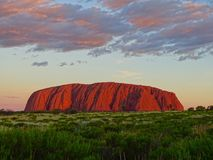 View of Uluru from the sunset viewing area. Uluru, Northern Territory, Australia 02/22/18. View of the ever changing colours of Uluru at sunset from a designated stock image