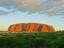 View of Uluru from the sunset viewing area. Uluru, Northern Territory, Australia 02/22/18. View of the ever changing colours of Uluru at sunset from a designated stock images