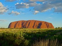 View of Uluru from the sunset viewing area. Uluru, Northern Territory, Australia 02/22/18. View of the ever changing colours of Uluru at sunset from a designated stock photos