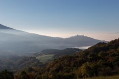 View of Umbria valley with hills full of autumn trees and Assisi. Town in the background, above some layers of mist Stock Photography