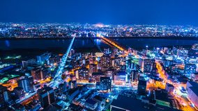 Japan Osaka City Skyline Timelapse. View from Umeda Sky Building. Overlooking the bridges with traffic and train going in and out of the Osaka city center. Zoom stock video footage