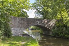 View under arch bridge in Cheshire UK. Arch bridge view with narrow boat on the Trent and Mersey Canal in Cheshire England United Kingdom Royalty Free Stock Photos
