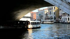 View from under the bridge on the Grand Canal. By Channel float large passenger ships, motorboats and gondolas stock footage