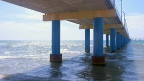 View under the ocean pier on sandy beach with waves at sunny day. stock video