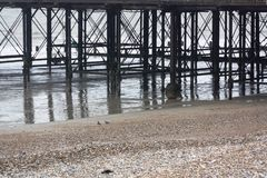 View under the pier. A view under the pier at Bognor Regis at low tide, showing debris on the metal structure, reflections in the water and shingle beach Stock Images