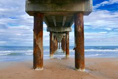 View under an ocean pier with cloudy blue sky. View under a wooden and cement ocean pier that`s stretching from the beach out to the ocean in St. Augustine royalty free stock image