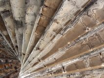 View underneath old eroded brown worn concrete spiral stairs forming a geometric abstract. A view underneath old eroded brown worn concrete spiral stairs forming royalty free stock photography