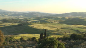 View into Val d´Orcia, Tuscany. View on the green landscape of the Val d´Orcia in Tuscany in spring as the sun starts to set stock video footage
