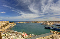 View on Valletta Grand harbor from the historic Upper Barraka garden area in Malta and  Fort St. Angelo and a ship leaving. View on Valletta Grand harbor from Royalty Free Stock Image