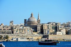 View of Valletta, Malta. View of Valletta city buildings and waterfront seen from Marsamxett Harbour with a tour boat in the foreground, Valletta, Malta, Europe Royalty Free Stock Photo
