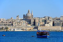 View of Valletta, Malta. View of Valletta city buildings and waterfront seen from Marsamxett Harbour with a tour boat in the foreground, Valletta, Malta, Europe Stock Image
