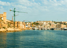 View of Valletta port with cranes and boats. View of Valletta city and port with cranes and boats from the sea, Malta Royalty Free Stock Photo