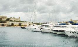 View of Valletta`s Fort St Elmo and yachts moored at Msida Marina stock image