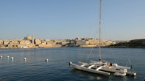 The view on Valletta and sail yacht with Ukrainian flag in sunset. Sliema, Malta stock footage