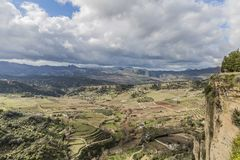 View of a valley with areas of pasture and horticultural surrounded by mountains seen from the city Ronda. A sunny day with a blue sky with abundant white royalty free stock photography