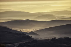 View of a valley in a beautiful early morning. A view of a valley in a beautiful early morning with fog between hills Royalty Free Stock Images