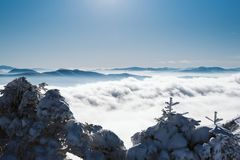 A view of the valley covered by the snow from the top of a snowy mountain on a sunny day royalty free stock photography