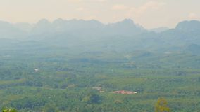View of the valley with mountains in the background. Pointed rocks on the horizon. Green forests onthe plain. Typical Asian Landscape. Virgin nature of the stock footage