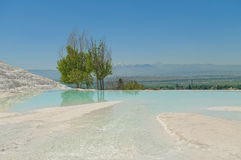 View of valley and mountains from white travertine terrace. Of Pamukkale UNESCO World Heritage Site with green trees and flowing spring water at foreground Stock Image