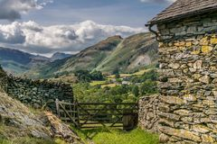 A view of a valley from a stone barn and a farm gate. stock images
