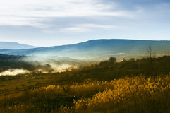 View of the valley at sunset. Yellow grass and blue hills in the background shrouded in mist at sunset Stock Images