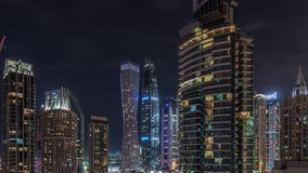 View of various skyscrapers and towers in Dubai Marina from above aerial night timelapse. Illuminated modern buildings in urban skyline stock video footage