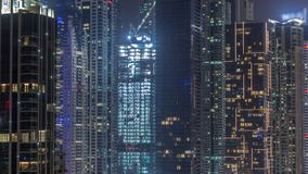 View of various skyscrapers and towers in Dubai Marina from above aerial night timelapse. Illuminated modern buildings in urban skyline with construction site stock footage