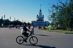 View of VDNH park in Moscow. Woman riding a bicycle. Royalty Free Stock Images