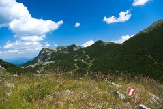 View from Velebit. Panorama of Velebit, footpath with red tourist marking, blue sky with clouds, Croatia Royalty Free Stock Photography