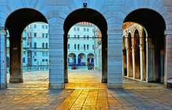 View on Venice Rialto bridge zone with canal grande and Fondaco dei Tedeschi facade through three ancient stone arched with beauti stock images