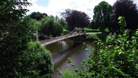 View of Victorian suspension footbridge over the river Wye in Hereford. stock video footage