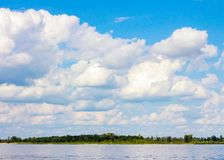 View of the village across the river. Wide river, sky with clouds, trees. stock photos