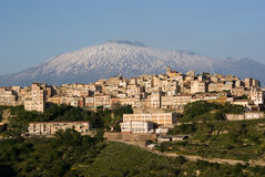 View of village and belltower. View of dwellings and belltower in the city of Centuripe in Sicily, on background the volcano Etna partly snowy stock images