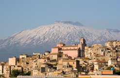 View of village and belltower on background Etna. View of dwellings and belltower in the city of Centuripe in Sicily, on background the volcano Etna partly snowy stock images