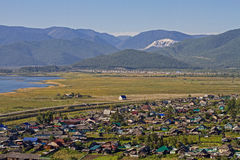 View on the village with colorful houses on the shore of Lake Baikal in the mountains in the summer. Royalty Free Stock Photo