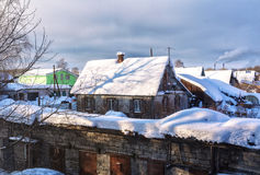 View of the village houses in winter. On landscape photography of the village, one-story houses, chimneys, winter, snow drifts, sunny evening, the old wooden Stock Photo