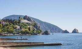 View of the village, located on the rocky shore of the Black sea, and the breakwaters in the foreground.  royalty free stock photography