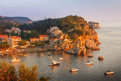 View of the village Przno on a rocky beach in a picturesque bay at sunset. Montenegro. Royalty Free Stock Images