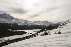 A view of a village in the snow covered landscape and mountains in the alps switzerland.  Stock Photography