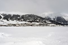 A view of a village in the snow covered landscape and mountains in the alps switzerland.  Royalty Free Stock Photography