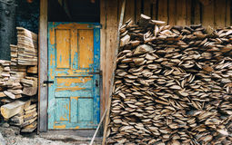 View at a village storage house for tools and fire woods. Vintage painted door in blue color. Paint is partially pilled off. Fire woods stored under a roof Stock Photos