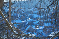 View of village through tree branches in winter. A view of the village through tree branches in winter Royalty Free Stock Photos